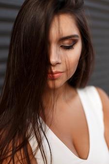 Close-up portret van een jonge mooie vrouw met make-up in witte jurk op een donkere achtergrond