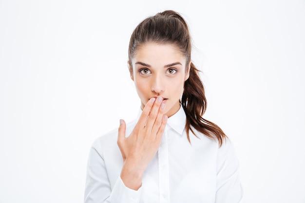 Close-up portret van een jonge mooie zakenvrouw die haar mond bedekt met palm geïsoleerd op een witte muur