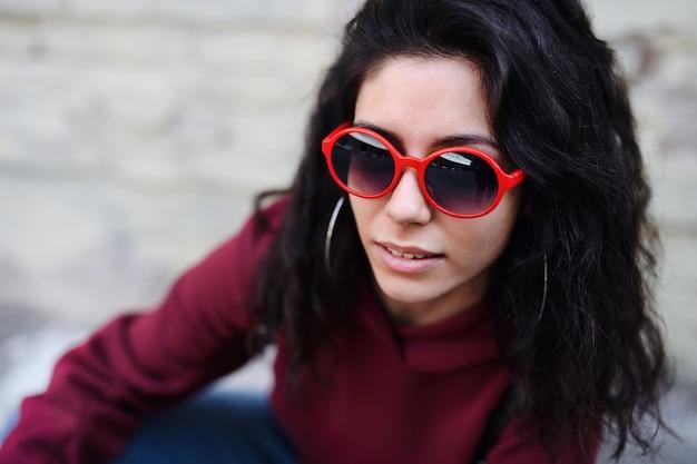 Close-up portret van een jonge vrouw met een zonnebril die buiten op straat in de stad staat.
