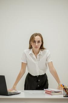 Close-up portret van een jonge zelfverzekerde vrouwelijke officemanager op haar werkplek, klaar voor zakelijke taak.