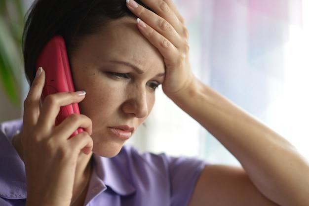 Close-up portret van een jonge, zieke vrouw die naar de dokter belt