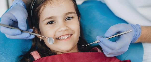 Close-up portret van een kaukasisch meisje met een onderzoek bij de pediatrische tandarts terwijl lachend aan de voorkant