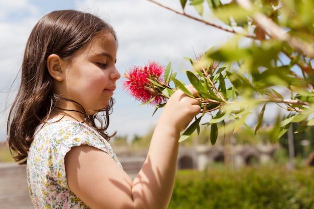 Close-up portret van een klein blank kind dat een bloem in de open lucht overweegt. ruimte voor tekst.
