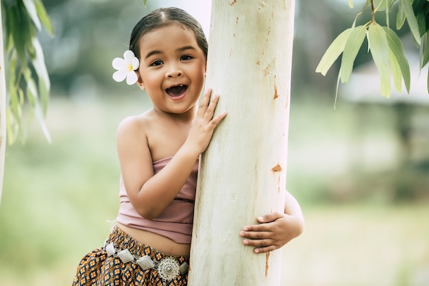 Close-up, portret van een klein meisje in thaise traditionele kleding en witte bloem op haar oor gezet, sta en omhels de stam van de boom, lach, kopieer ruimte