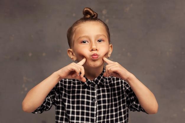 Close-up portret van een klein mooi meisje met blond haar opgetrokken in een knot. het kind speelt en poseert. spelletjes voor kinderen.