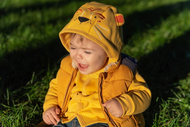 Close-up portret van een kleine babyjongen die huilt en uitkijkt, de baby zit op het gras en huilt