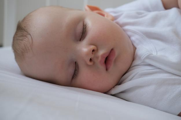 Close-up portret van een kleine slapende baby in een wieg.