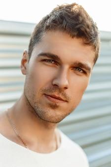 Close-up portret van een knappe jonge man met een baard in een zomerdag.