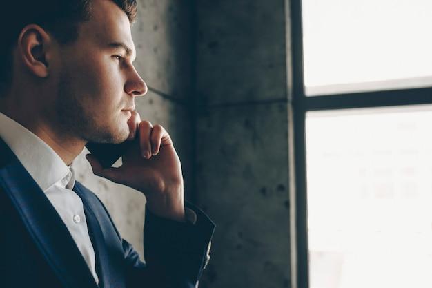 Close-up portret van een knappe jonge ondernemer praten aan de telefoon terwijl hij door een raam in zijn kantoor kijkt.