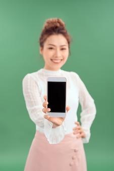 Close-up portret van een lachende aziatische vrouw die een leeg scherm mobiele telefoon toont terwijl ze geïsoleerd staat over groene achtergrond.