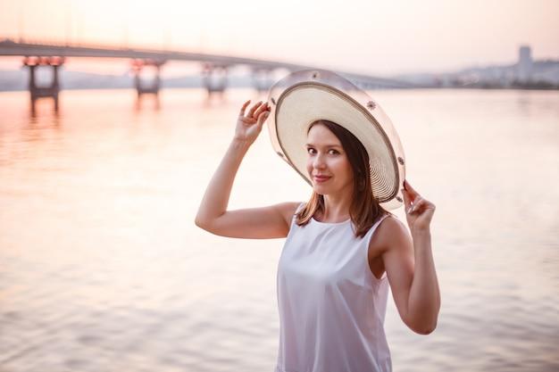 Close-up portret van een lachende blanke vrouw in een witte jurk die haar handen vasthoudt aan de rand van een st...