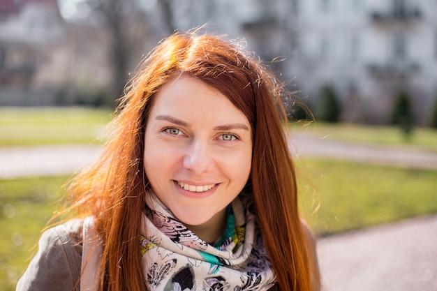 Close-up portret van een lachende jonge roodharige meisje met lang haar camera kijken terwijl buitenshuis staan, lentetijd