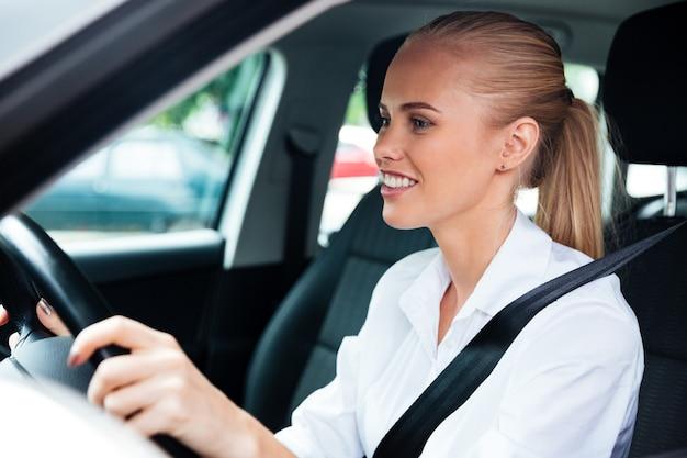 Close-up portret van een lachende jonge zakenvrouw die haar auto bestuurt