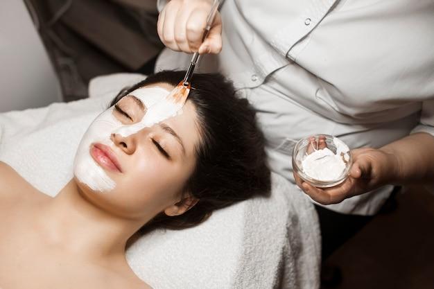 Close-up portret van een leuke vrouw leunend op een bed met gesloten ogen terwijl de helft van haar gezicht met een wit masker is.