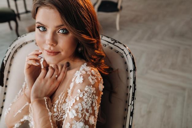 Close-up portret van een luxe bruid in een trouwjurk in de ochtend in haar interieur.