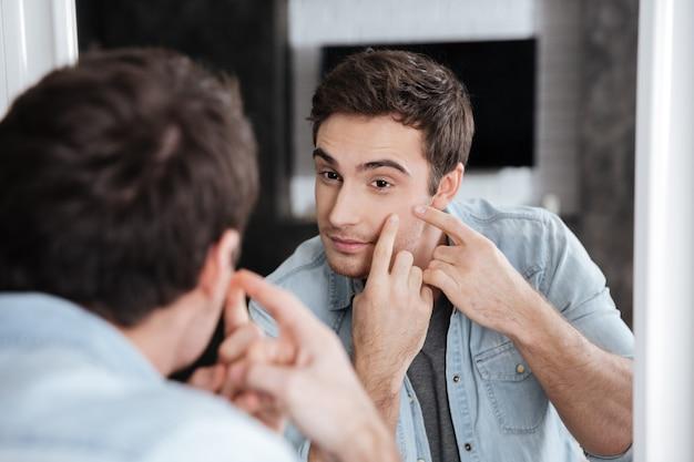 Close-up portret van een man die naar zichzelf in een spiegel kijkt en in zijn puistjes knijpt