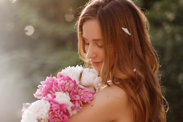 Close-up portret van een model met bloemen in de zomer bij zonsondergang. in de haarblaadjes.