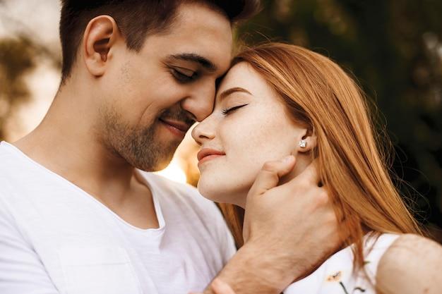 Close-up portret van een mooi jong koppel omarmen voordat kussen glimlachend tegen zonsondergang tijdens het daten in hun vakantietijd.