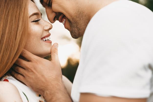 Close-up portret van een mooi kaukasisch paar lachend van aangezicht tot aangezicht met gesloten ogen voordat ze buiten kussen tegen zonsondergang tijdens het daten.