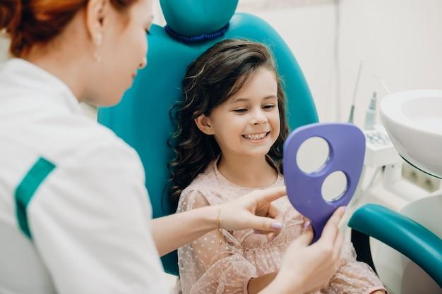 Close-up portret van een mooi klein meisje in de spiegel kijken naar de tandarts na onderzoek. glimlachend klein jong geitje dat bij tandheelkundig onderzoek glimlacht.