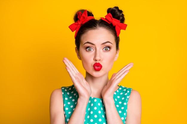 Close-up portret van een mooi lief meisje dat luchtkus, mollige lippen verzendt, geïsoleerd over een levendige gele kleurachtergrond