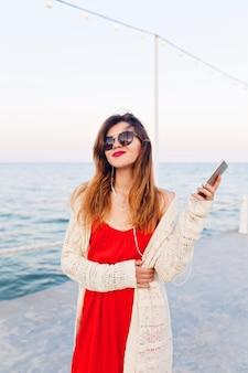 Close-up portret van een mooi meisje in een rode jurk en witte jas op een pier, glimlachend en luisteren naar muziek op oortelefoons op een smartphon