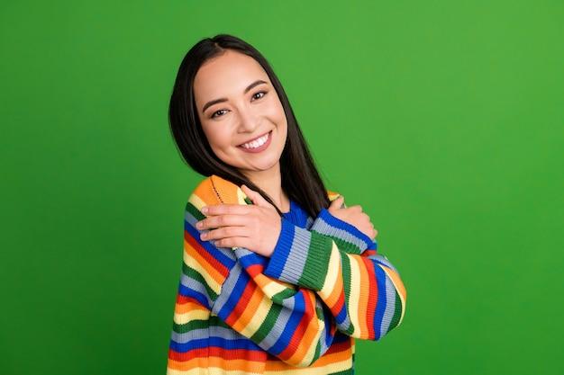 Close-up portret van een mooi teder vrolijk meisje met een gestreepte warme trui die zichzelf knuffelt, geïsoleerd over een heldergroene kleurachtergrond
