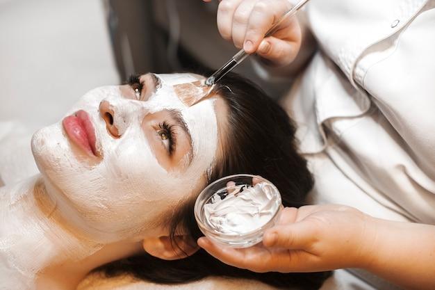 Close-up portret van een mooie blanke vrouw met een wit masker op haar gezicht gespeeld door een vrouwelijke handen.
