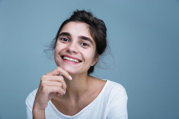 Close-up portret van een mooie jonge brunette vrouw met een wit t-shirt staande geïsoleerd over blauwe achtergrond, poseren, gezicht aan te raken