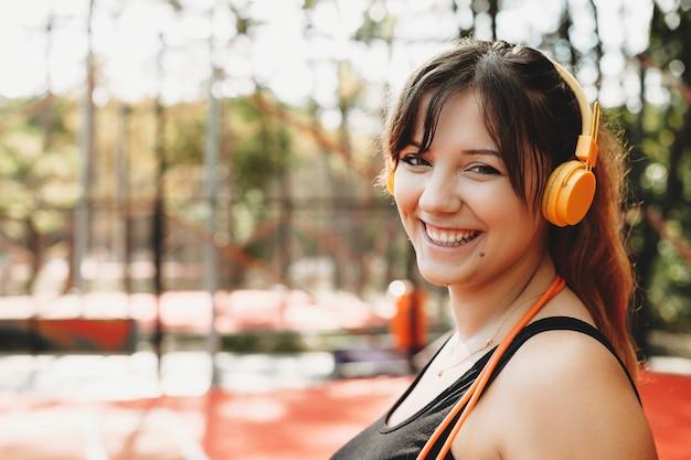 Close-up portret van een mooie jonge plus size vrouw kijken camera lachen terwijl het luisteren naar muziek ochtend cardio doen om af te vallen.