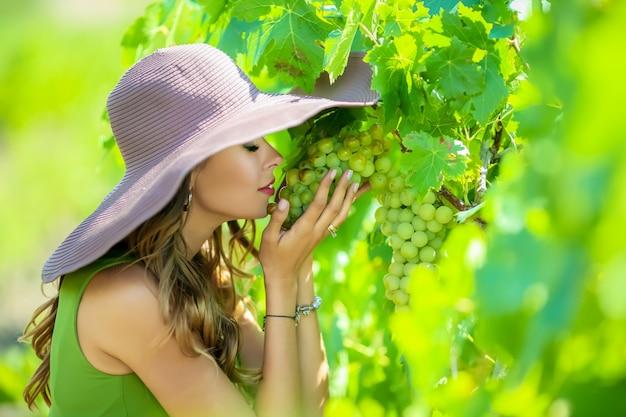 Close-up portret van een mooie jonge vrouw die een tros druiven in haar handen houdt