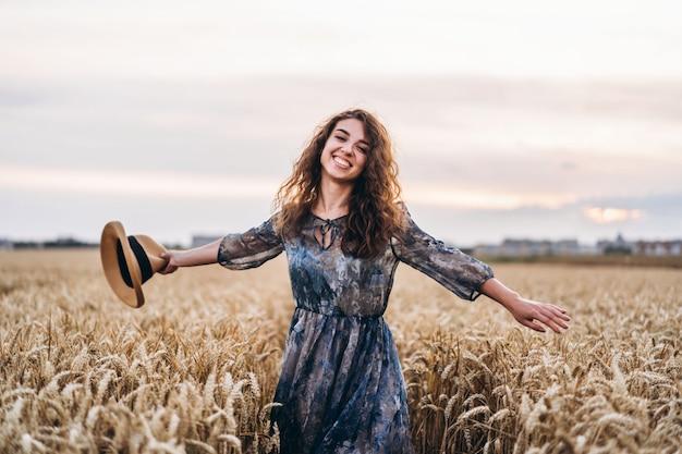 Close-up portret van een mooie jonge vrouw met krullend haar. vrouw in jurk en hoed staande in een tarweveld