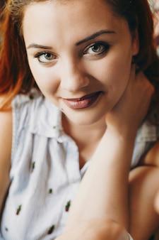 Close-up portret van een mooie plus size vrouw met rood haar kijken naar de camera lachend terwijl ze een hand op haar nek houdt.