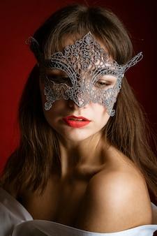 Close-up portret van een mooie sexy vrouw in een masker op een rode achtergrond, rode lippen