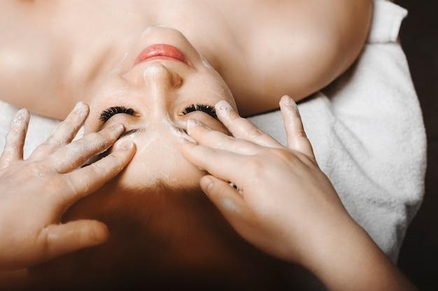 Close-up portret van een mooie volwassen vrouw doet anti leeftijd gezichtsmassage met schuim door een vrouwelijke schoonheidsspecialist in een wellness-kuuroord.
