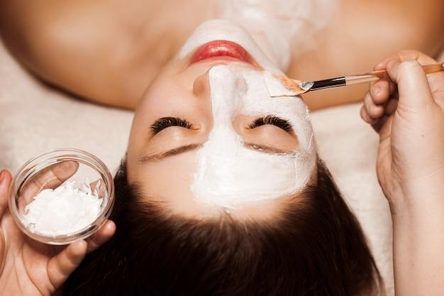 Close-up portret van een mooie vrouw doet een routine wit masker huidverzorging in een kuuroord.