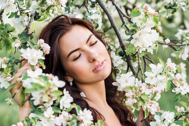Close-up portret van een mooie vrouw in een lentetuin. een meisje met haar ogen dicht ademt de geur van bloeiende bomen in.