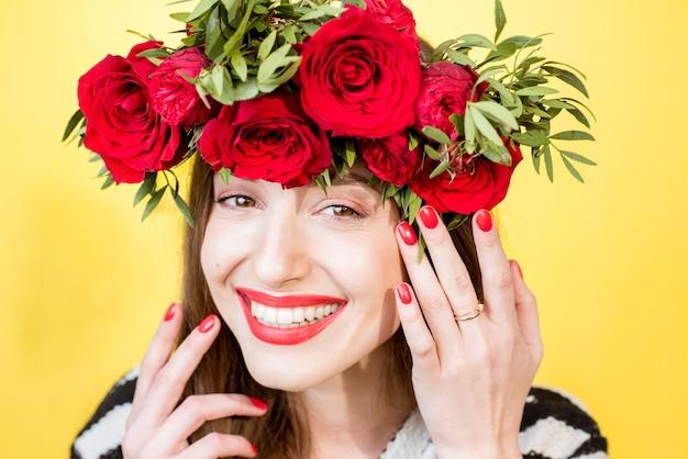 Close-up portret van een mooie vrouw in trui met krans gemaakt van rode rozen op de gele achtergrond