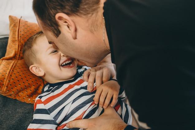 Close-up portret van een mooie zoontje spelen met zijn vader in de ochtend in het bed bij hen thuis.