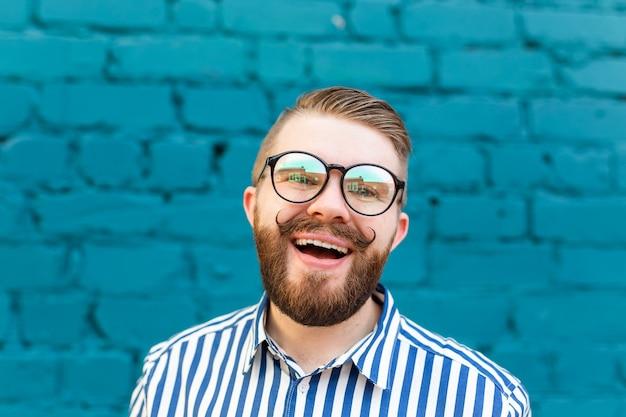 Close-up portret van een nieuwsgierige verrast jonge man in glazen met een snor en baard poseren op een muur van blauwe wazig bakstenen muur. concept van verrassing en schokkende informatie. copyspace
