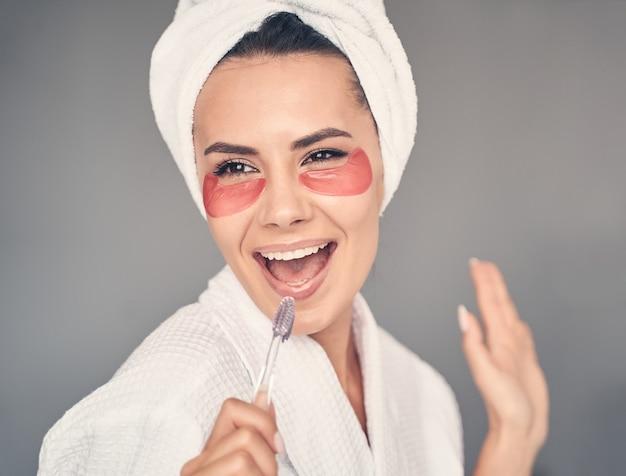Close-up portret van een ondeugende blanke jonge vrouw met een tandenborstel die voor de voorkant poseert