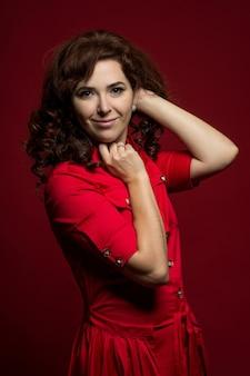 Close-up portret van een roodharige vrouw in een rode jurk