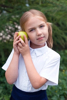 Close-up portret van een schattig klein gelukkig meisje in een schooluniform dat een appel eet. school. onderwijs.