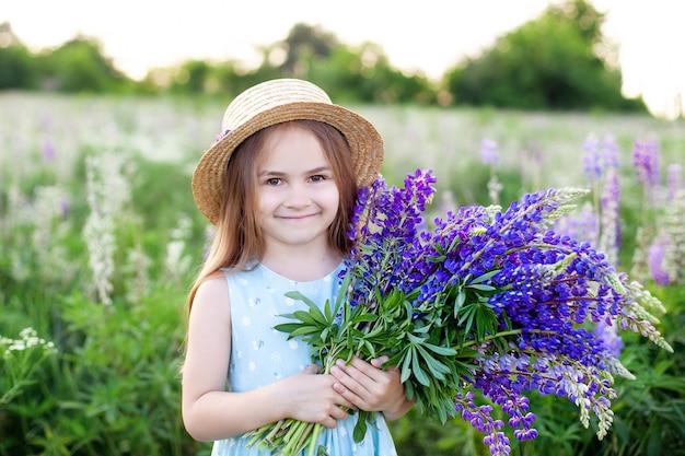 Close-up portret van een schattig klein meisje in een hoed in een veld van lupinen. meisje met een boeket van paarse bloemen in de muur van een veld van lupinen. het concept van de kindertijd. kopieer ruimte.