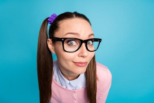 Close-up portret van een schattig nieuwsgierig vrolijk studentemeisje dat naar jou kijkt