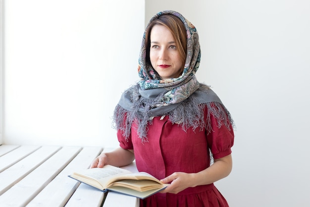 Close-up portret van een schattige jonge dromerige vrouw met een boek in haar hand die uit het raam kijkt en ergens aan denkt. conceptliefhebbers van klassiekers en literatuur.