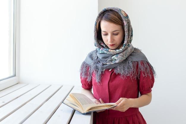 Close-up portret van een schattige jonge dromerige vrouw met een boek in haar hand kijkt uit het raam