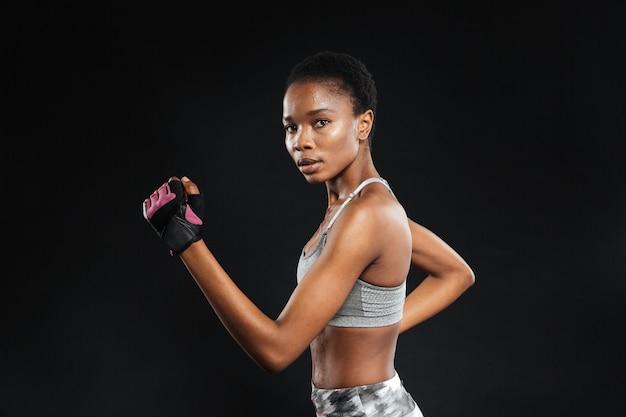 Close-up portret van een sportvrouw die geïsoleerd op een zwarte muur loopt