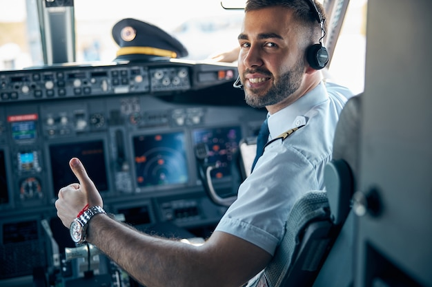 Close-up portret van een stralende lachende man piloot in uniform die laat zien alsof hij op de stoel zit in de cockpit van een civiel vliegtuig