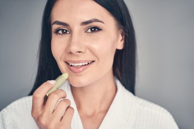 Close-up portret van een tevreden meisje met een lipgloss die voor haar kijkt